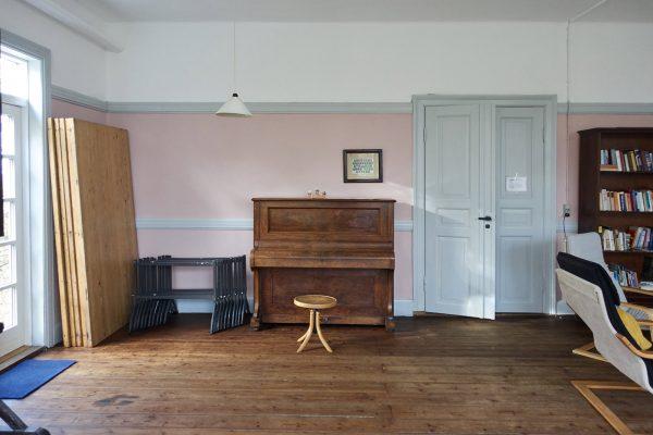 Großer Seminarraum mit Klavier und Bibliothek