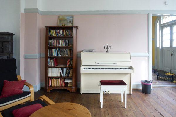 Seminarraum in Rosa. Das weiße Klavier.