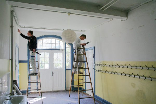Malerarbeiten in der Eingangshalle. Man sieht noch das urspüngliche Farbschema Gelb Blau Weiß.